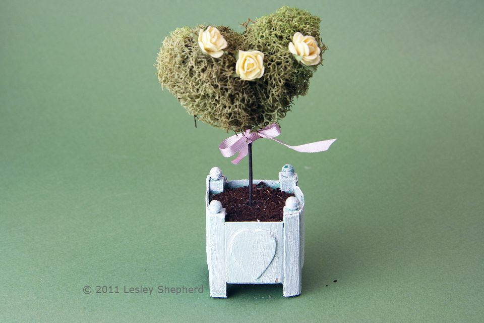 A moss covered miniature heart is trimmed and decorated to make a miniature topiary.
