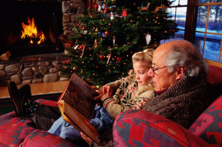 Grandfather reading to granddaughter (6-8) on sofa