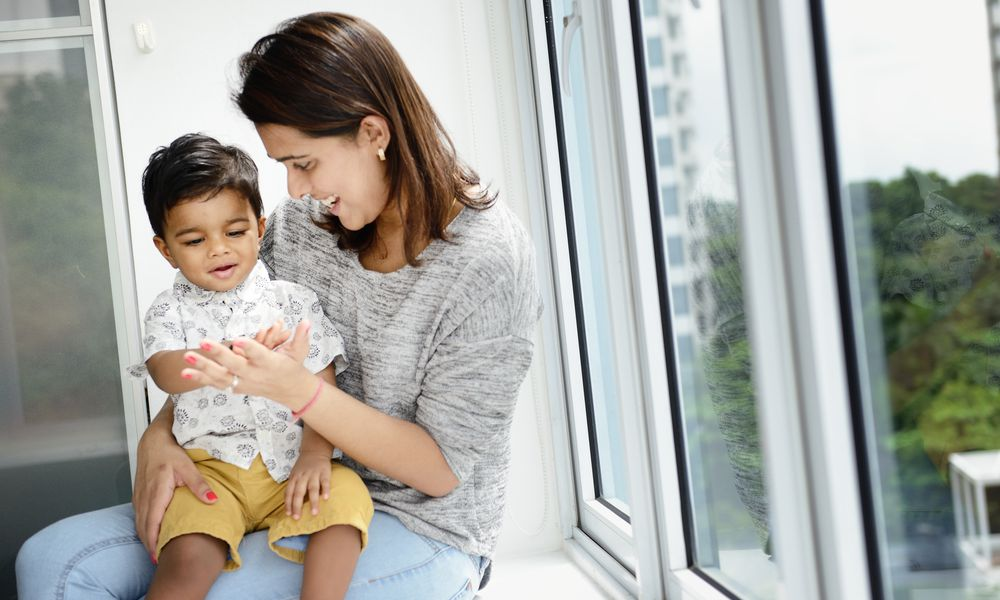 Mom sitting with toddler on a window sill