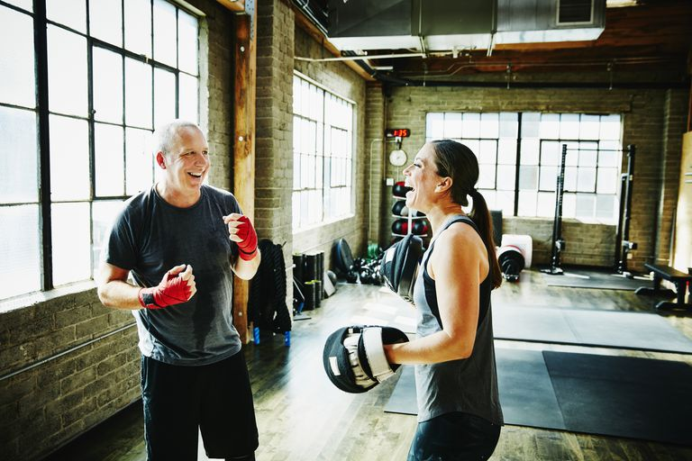 Man boxing with trainer in gym
