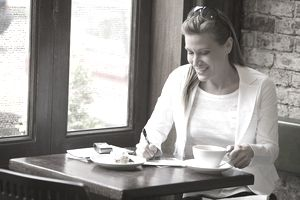 woman writing note in cafe