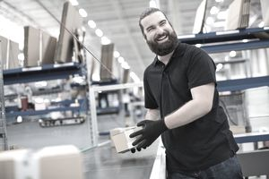 smiling man pulling product off conveyor belt