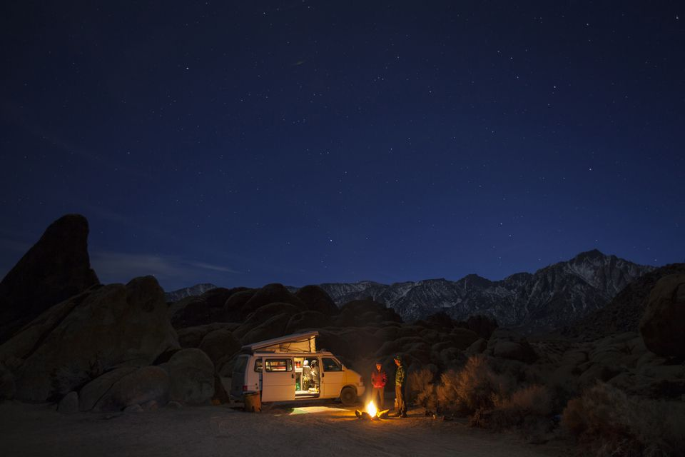 Two friends standing by campfire at night while camping in Alabama Hills Recreation Area, Lone Pine, California, USA