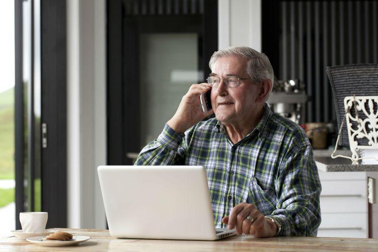 Senior with open laptop talking on phone