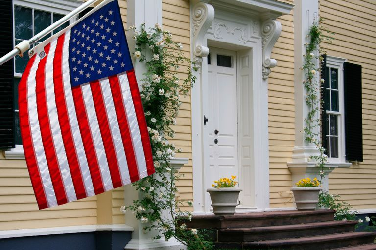 american flag hangs from the clapboard siding on a colonial home in boston massachusetts