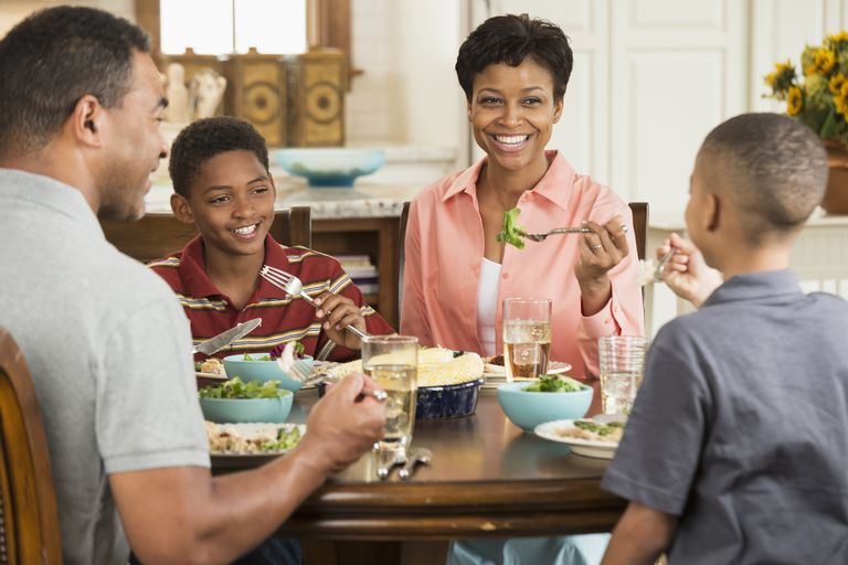 teaching kids how to disagree respectfully - family eating dinner together, talking and smiling