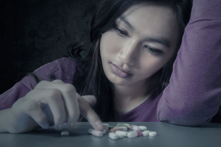 female student looking at depression pills