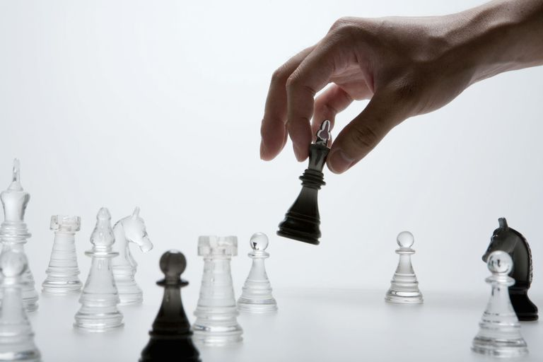 Chess Pieces with a Hand Moving One of the Pieces