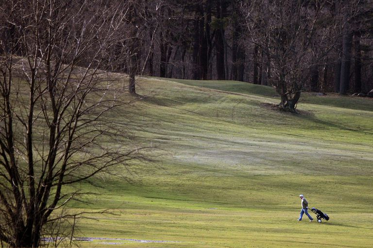 A lone golfer walks the Franklin Park Golf Course in Boston, Massachusetts