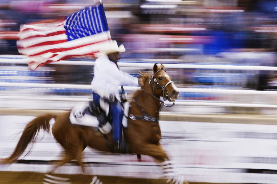 Blurred motion view of cowboy riding horse with American flag in rodeo