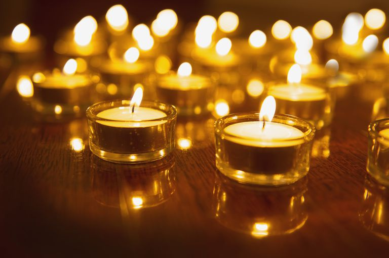 Close up of lit tea light candles on wooden table