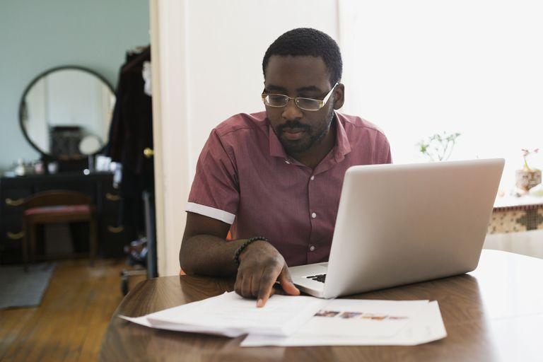 Focused man working at laptop reviewing paperwork