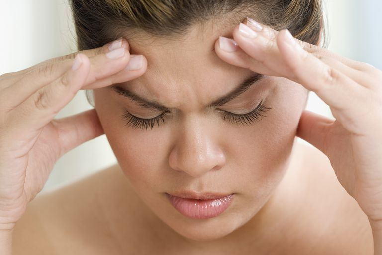 woman holding forehead in pain