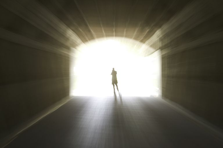 A figure passing into the light, perhaps to some past life experience.