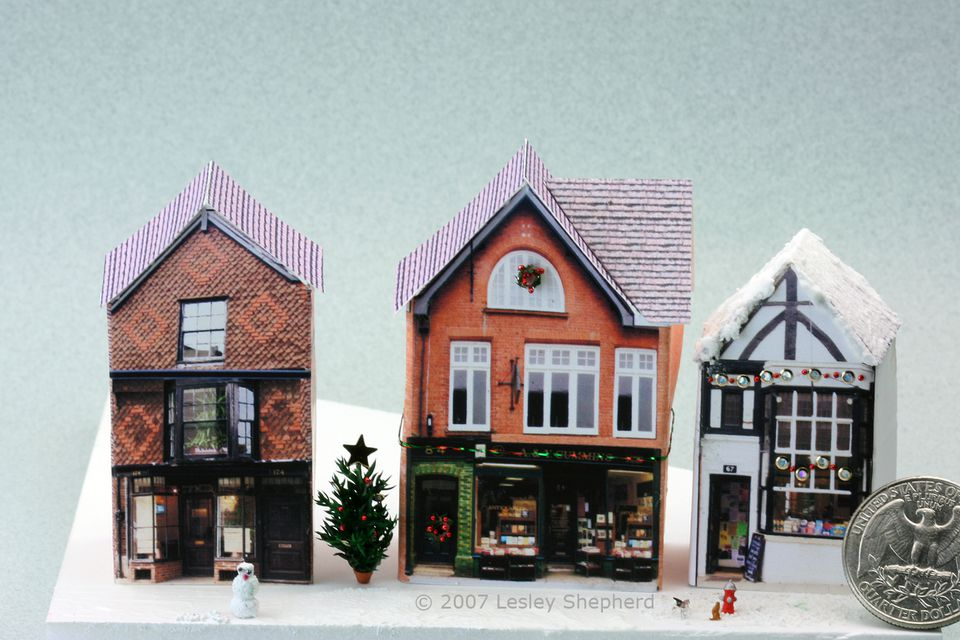 One eighth inch Christmas Wreaths, garlands and a tiny tree decorate an N Scale Village Shop.
