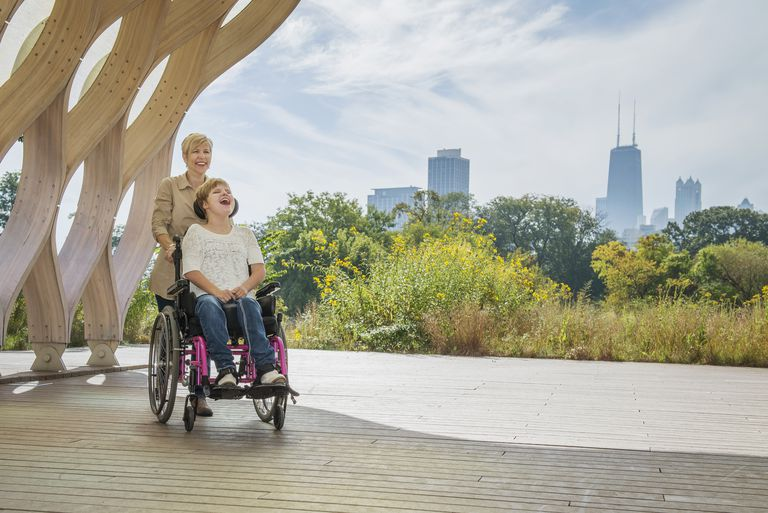 Mother pushing paraplegic daughter in wheelchair