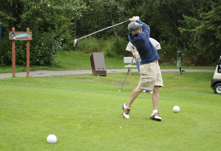 A golfer hits his drive from the white tees at a golf course.