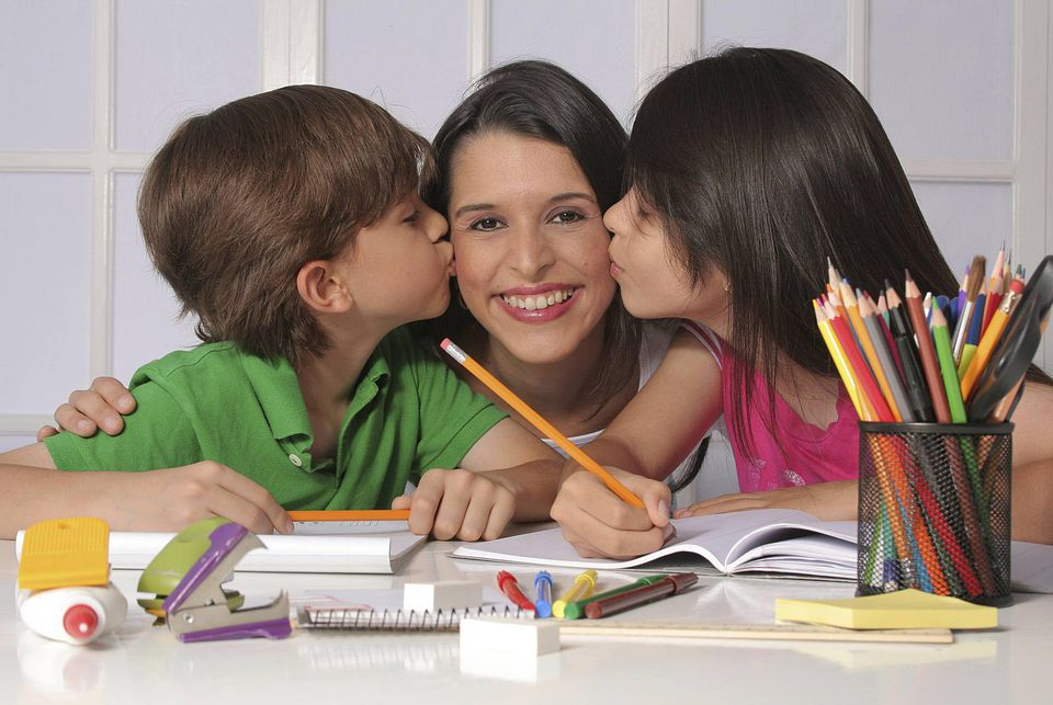A picture of a mom and her kids doing homework