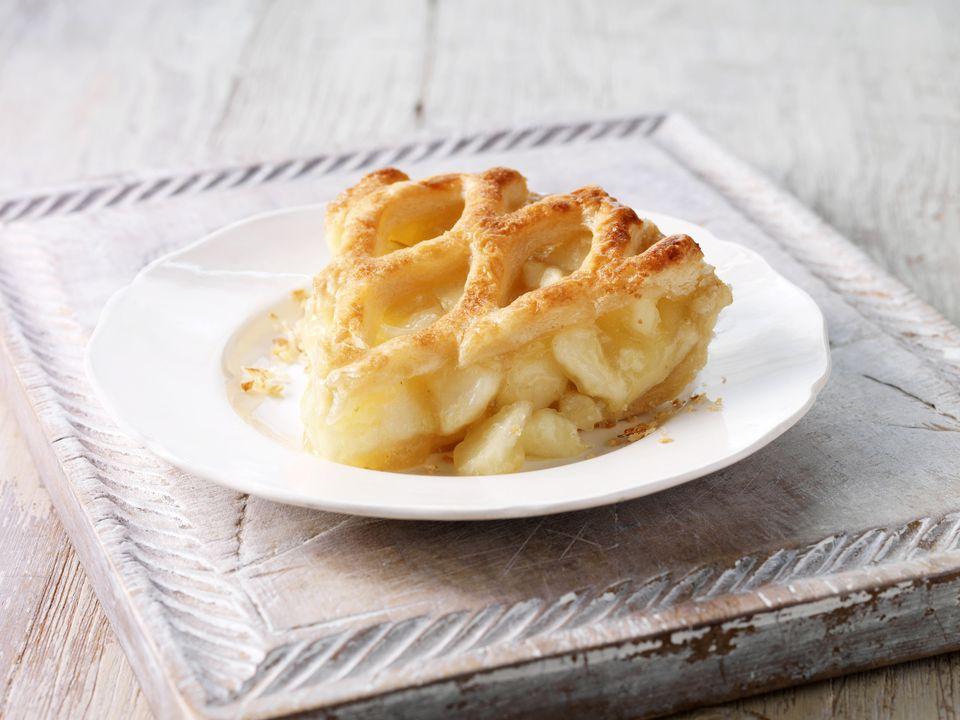 Apple pie slice on wooden chopping board