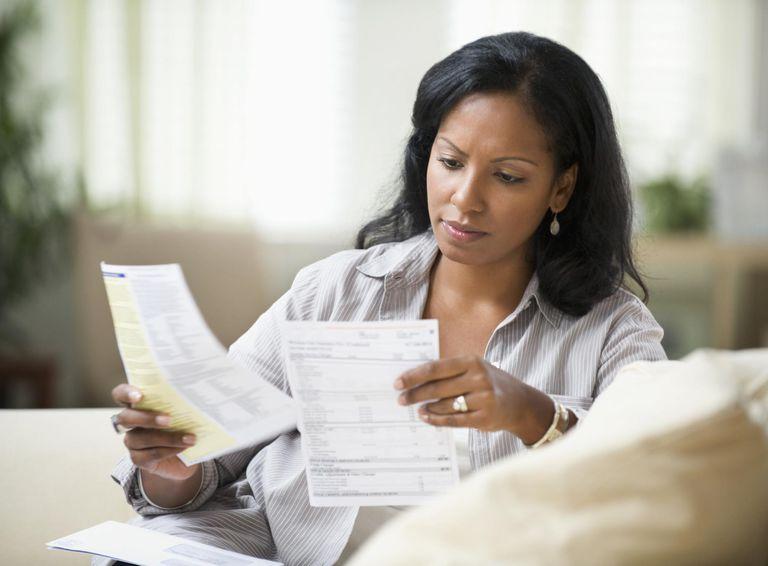 woman sitting on sofa reading bills