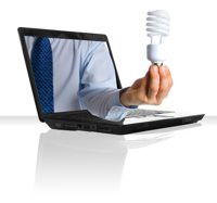 business man hand from computer holding an energy efficient compact bulb.