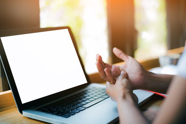 Young woman is getting Hand pain caused at office desk in front of laptop