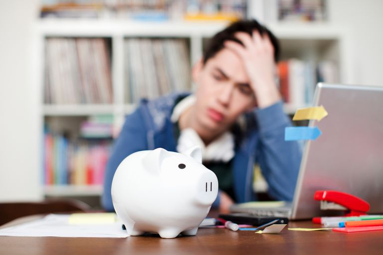 frustrated man looking at laptop and piggy bank