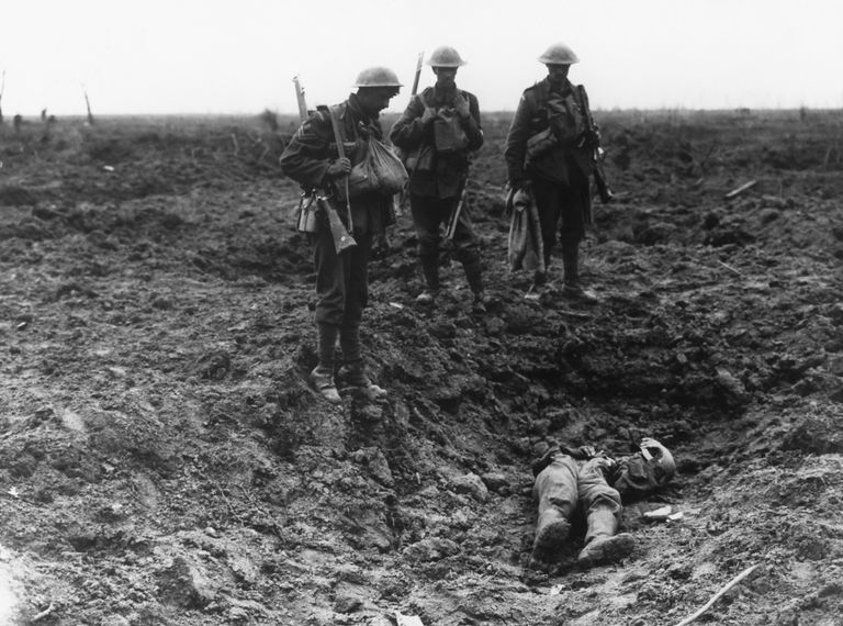 British Soldiers Stand Over Dead German In a Shell Crater