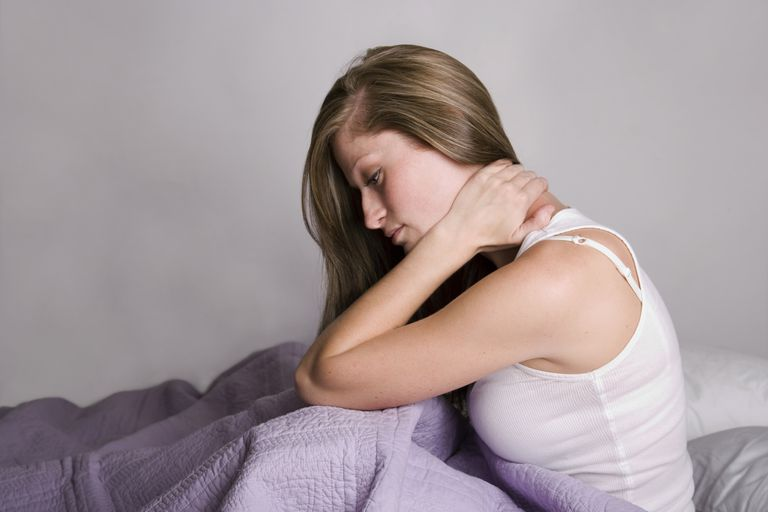 Young woman in bed with neck ache