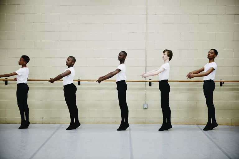 Male ballet dancers practicing at barre in studio