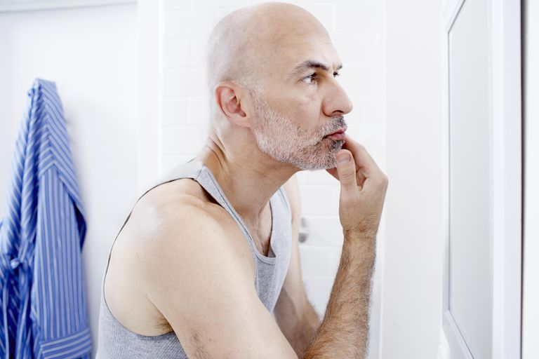 Man examining face in mirror