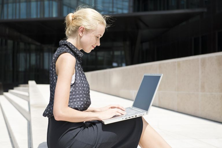 Businesswoman using laptop working outdoors