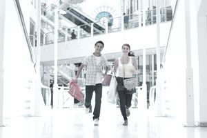 Smiling couple running with carrying shopping bags in mall