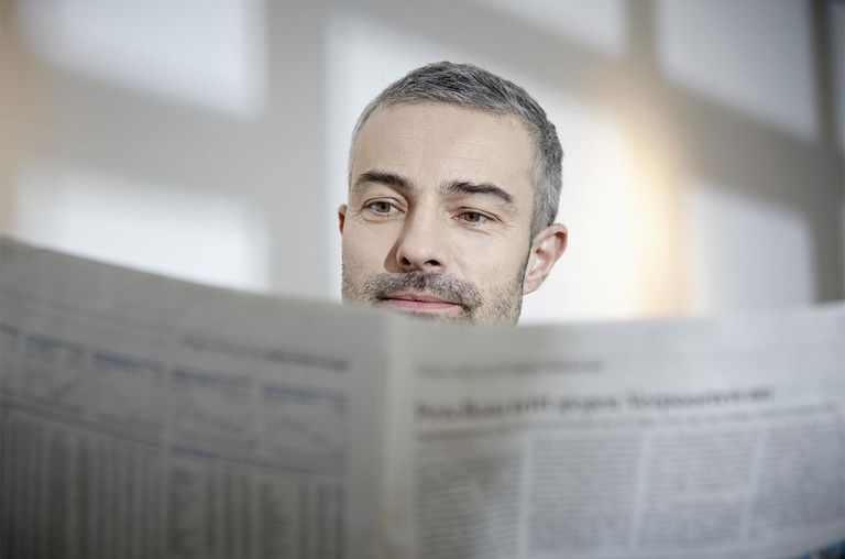 Mature man reading newspaper