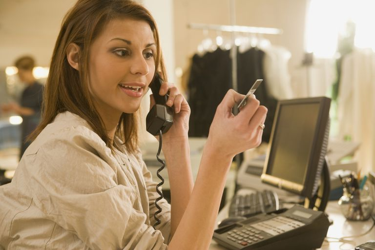 Woman on phone looking at credit card