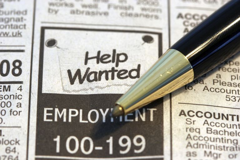 pen resting on help wanted ad in newspaper