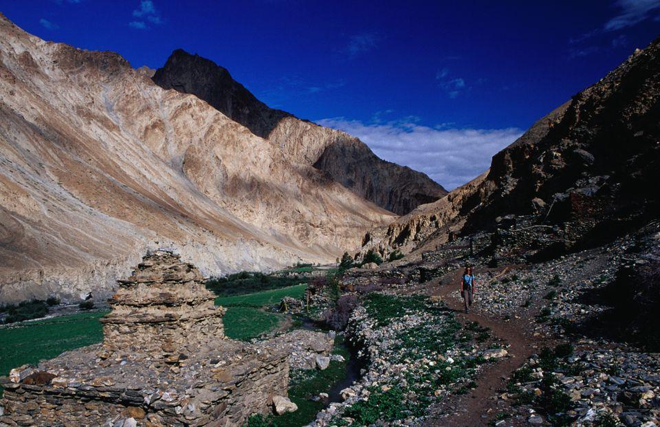 Trekkers walking through Chalak village in Markha Valley.