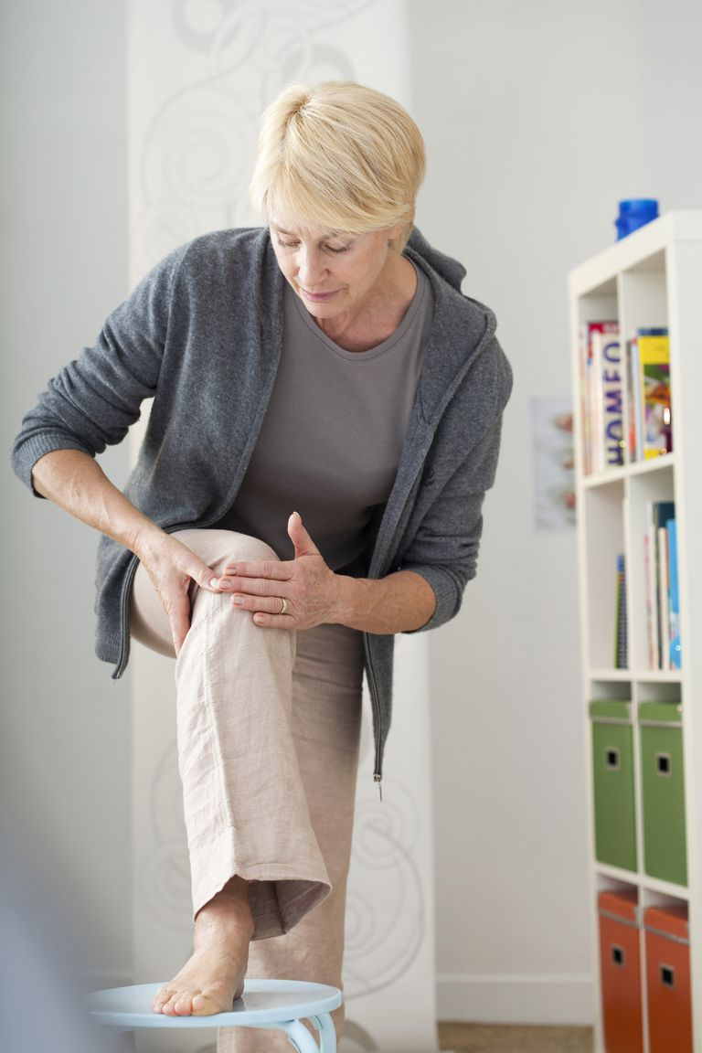 Mature woman holding knee in house