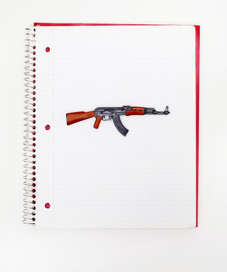 Assault rifle on spiral notebook .