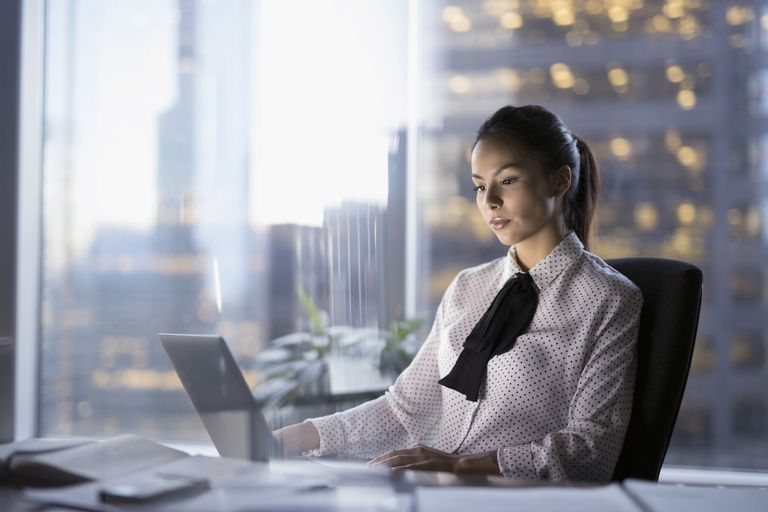 Female lawyer working late at laptop in urban office