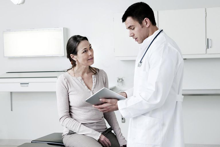 Doctor using tablet computer with patient