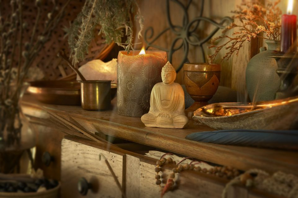 altar with Buddha, crystals, candles and sage smudging