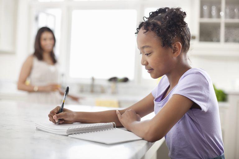 Girl doing homework in kitchen