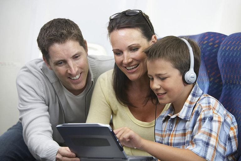 Mother, father and son using laptop on airplane, smiling