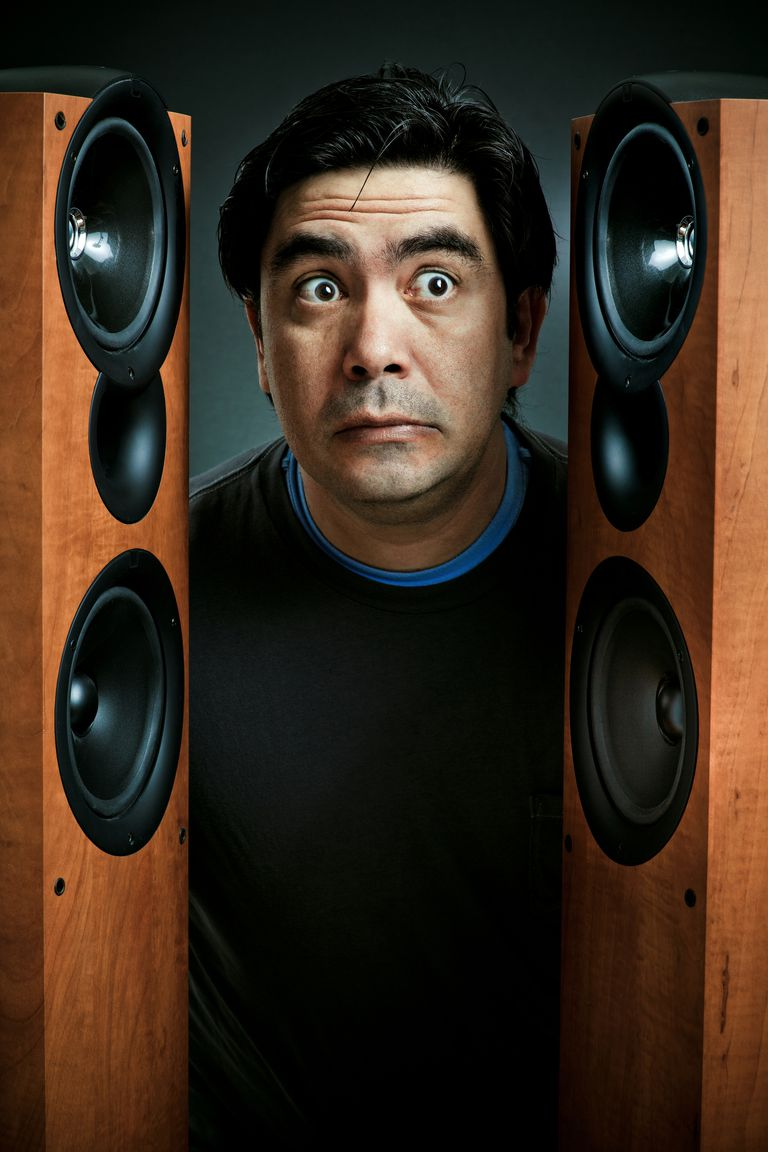 A man between a pair of stereo speakers