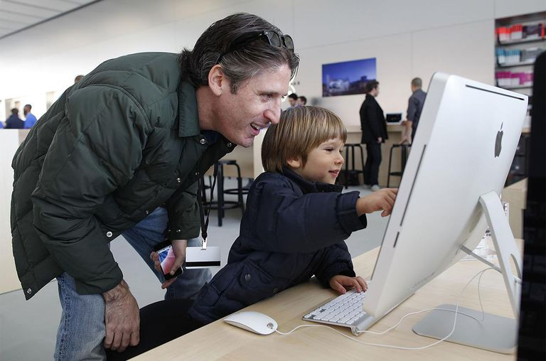 Apple emloyee Jason Roth (L) and his son Tyler Roth, 3, play with an iMac