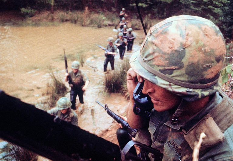 Officer talking on radio phone as line of soldiers crosses river below him