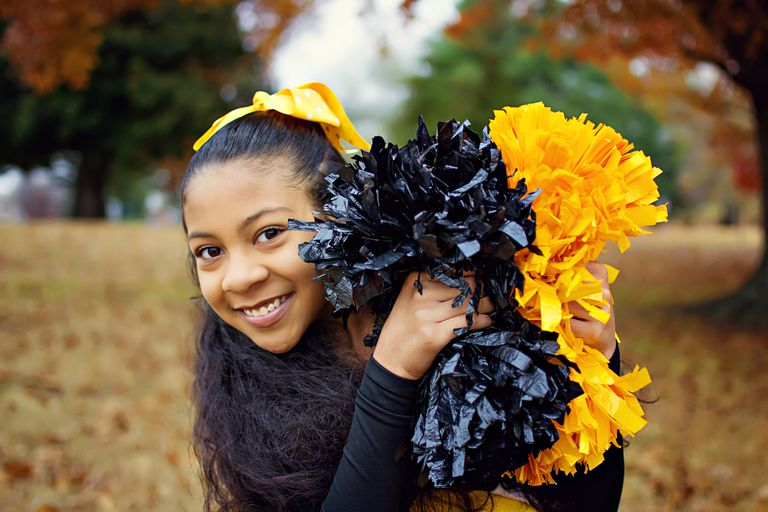 Cheerleader with black and gold pom-poms