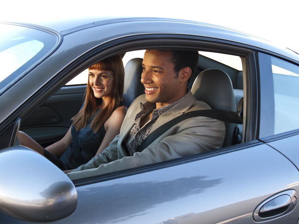 Smiling young couple in sports car
