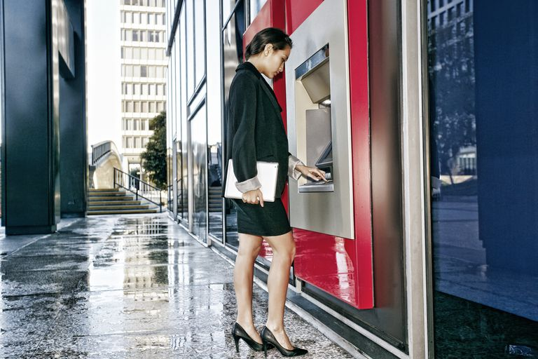 Mixed race businesswoman using ATM in city